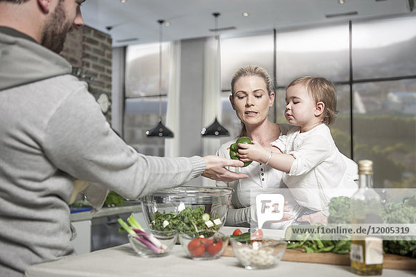 Familie mit Baby bei der Zubereitung einer gesunden Mahlzeit in der Küche