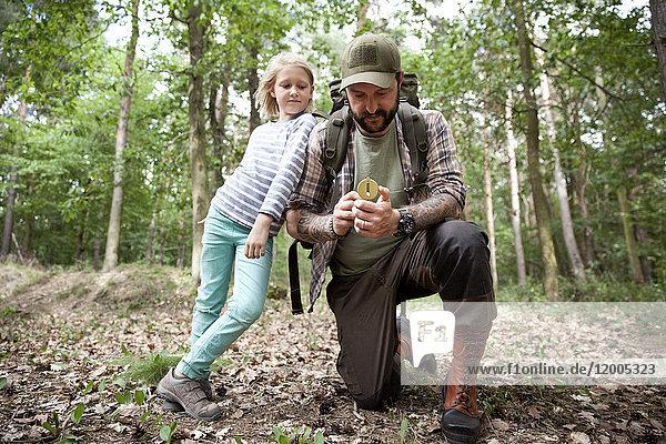Vater und Tochter mit Kompass im Wald