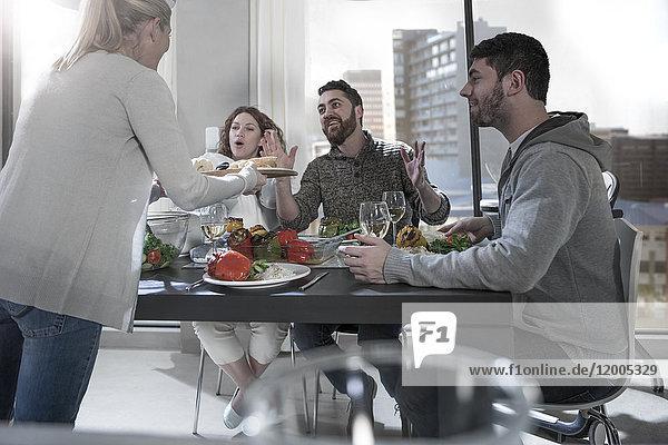 Frau serviert Essen für überraschte Freunde am Esstisch