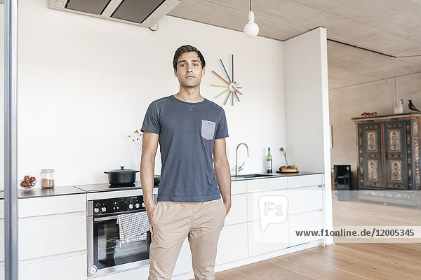 Young man standing in kitchen at home