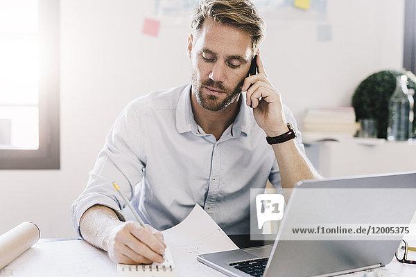 Porträt des Architekten am Telefon am Schreibtisch in seinem Büro
