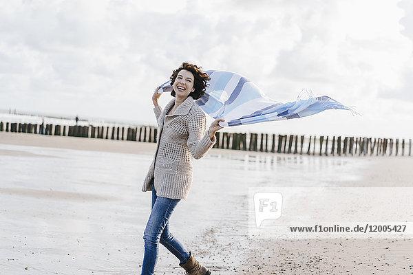 Glückliche Frau mit Tuch am Strand