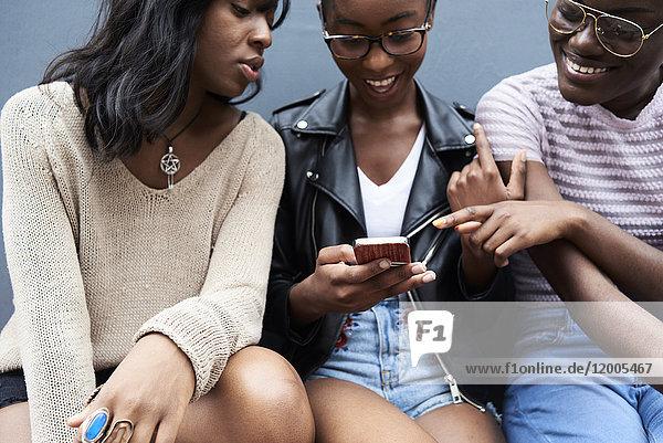 Drei Freunde sitzen Seite an Seite und schauen aufs Handy