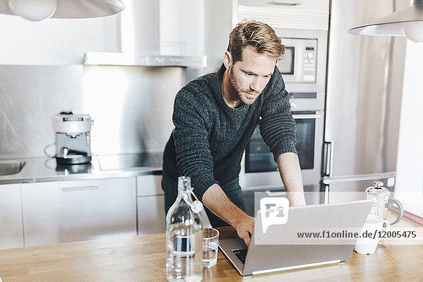 Portrait eines in der Küche stehenden Mannes mit Laptop