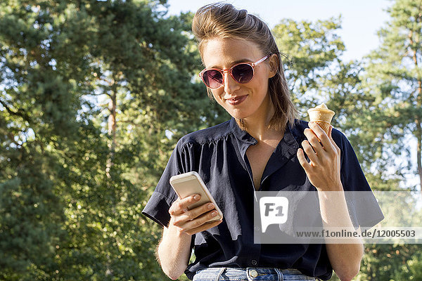 Young woman with ice cone using smartphone
