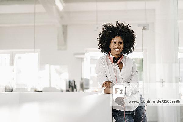 Porträt der lächelnden jungen Frau mit Kopfhörer im Büro