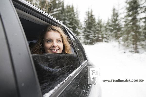 Junge Frau blickt aus dem Autofenster in die Winterlandschaft