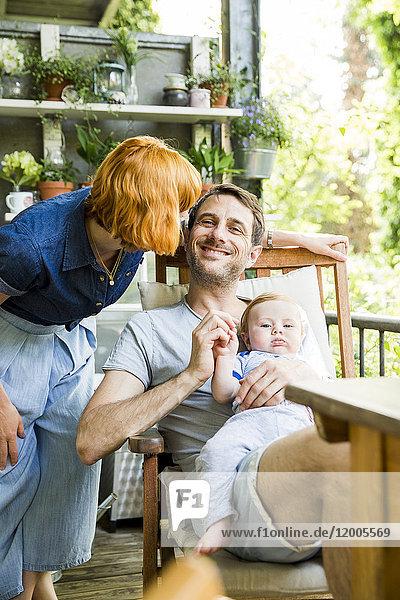 Glückliches Paar mit dem kleinen Sohn zusammen auf dem Balkon