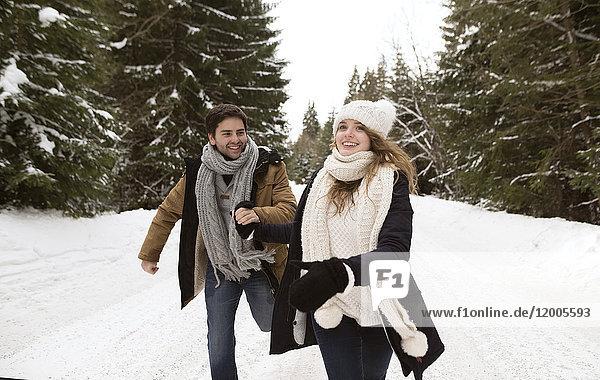 Glückliches junges Paar beim Laufen in verschneiter Winterlandschaft
