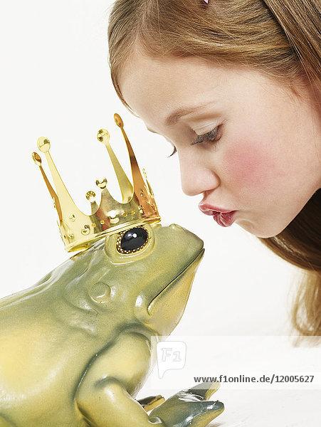 Portrait of little girl kissing frog king