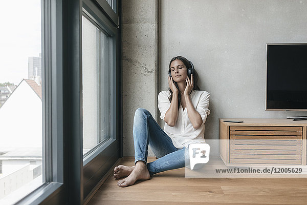 Relaxed woman listening to music at home