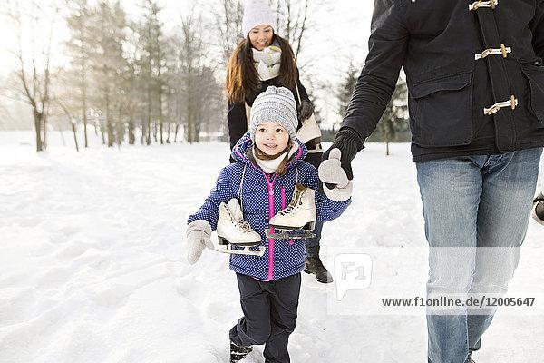 Kleines Mädchen beim Schlittschuhlaufen mit ihren Eltern