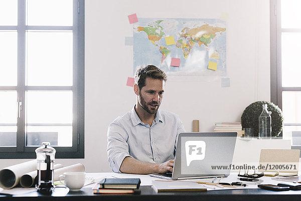 Architekt bei der Arbeit am Laptop am Schreibtisch in seinem Büro