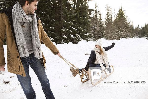 Glückliches junges Paar mit Schlitten im Winterwald