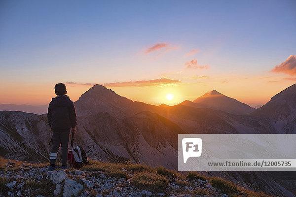 Italien  Abruzzen  Gran Sasso und Monti della Laga Nationalpark  Portella Berg  Wanderer beobachten Sonnenuntergang