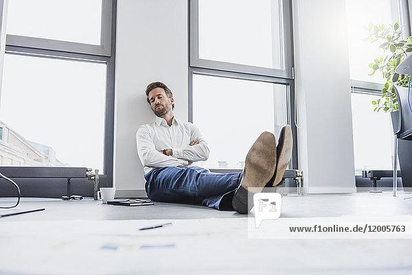 Geschäftsmann entspannt auf dem Boden seines Büros