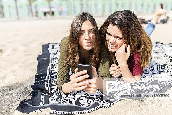 Zwei glückliche Freundinnen mit dem Handy am Strand