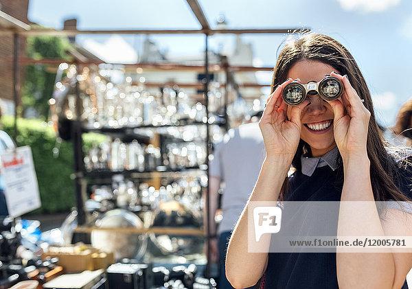 UK  London  Portobello Road  Porträt einer lachenden Frau  die durch ein altes Fernglas schaut.