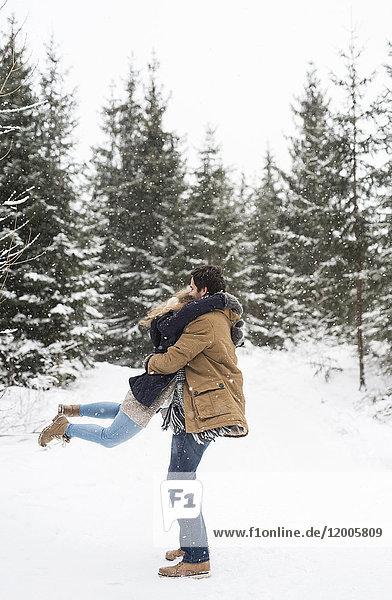 Fröhliches junges Paar beim Spaß im verschneiten Winterwald