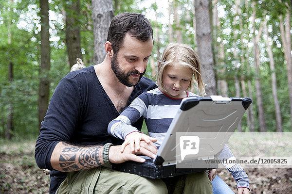 Vater und Tochter im Wald mit Laptop