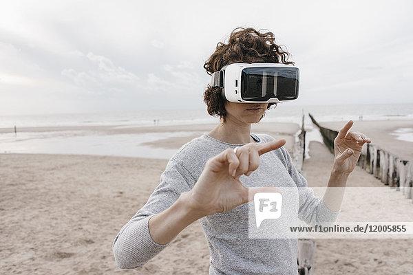 Frau am Strand mit VR-Brille