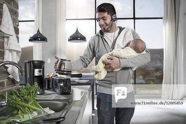Vater mit Kopfhörer macht Kaffee in der Küche und hält Baby