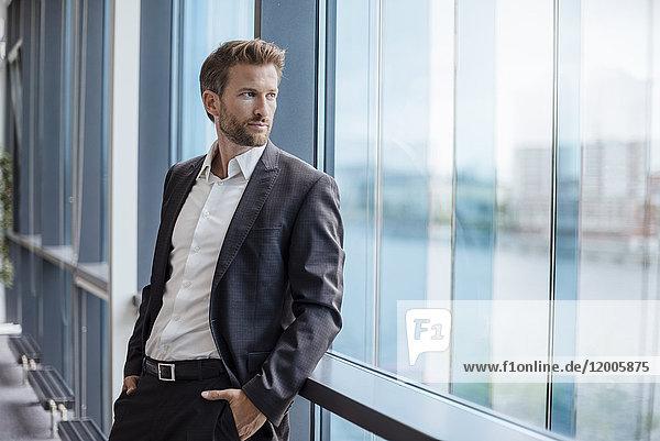 Porträt eines Geschäftsmannes mit Blick aus dem Fenster