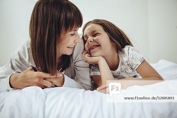 Glückliche Mutter und Tochter im Bett liegend