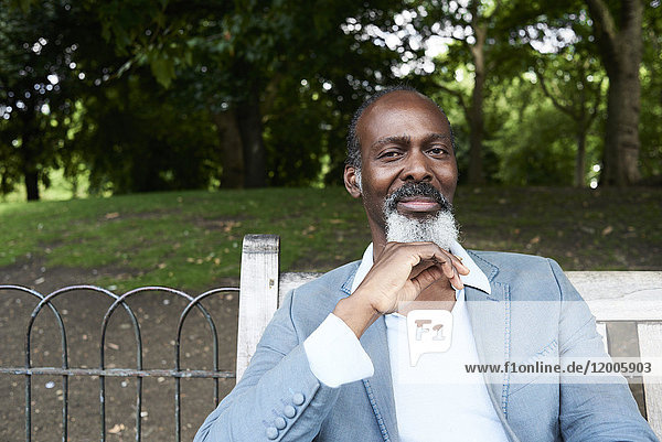 Portrait of bearded man sitting on park bench