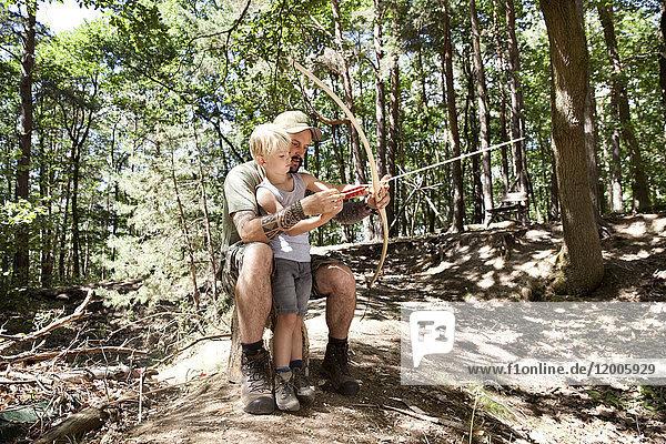 Vater und Sohn schießen mit Pfeil und Bogen im Wald