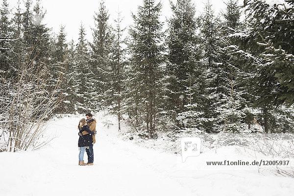 Fröhliches junges Paar im schneebedeckten Winterwald gegenüber stehend