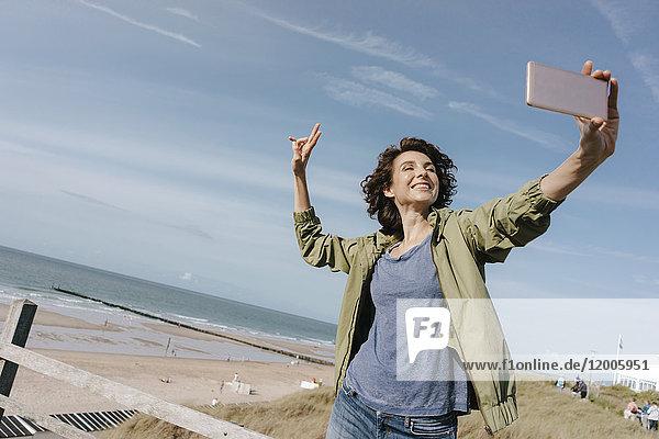 Glückliche Frau am Strand mit einem Selfie