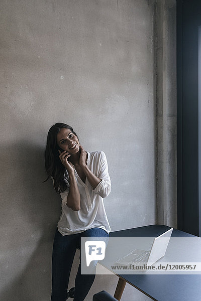 Porträt der lächelnden Frau an der Betonwand mit dem Handy