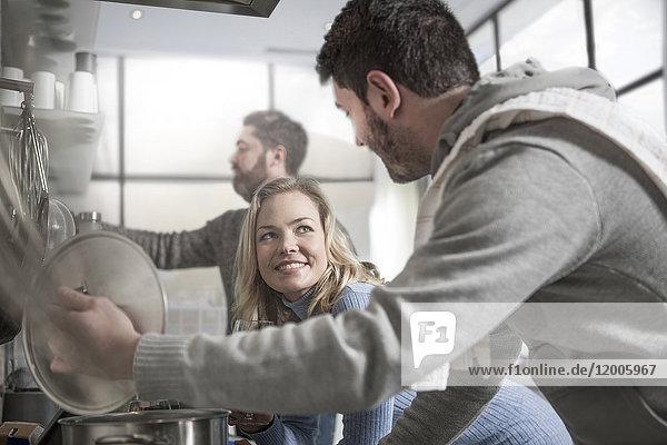 Paar beim Zubereiten von Speisen in der Küche mit dem Mann im Hintergrund