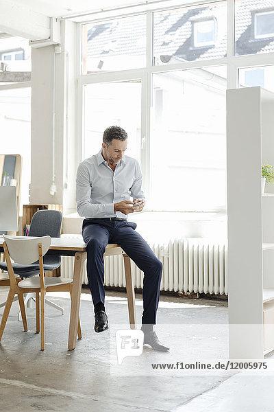 Geschäftsmann im Büro mit Blick auf Handy