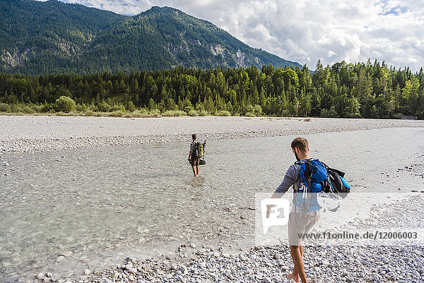 Germany  Bavaria  two hikers with backpacks crossing Isar River