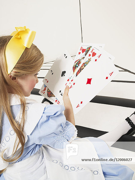 Little girl dressed up as Alice in Wonderland with oversized playing cards