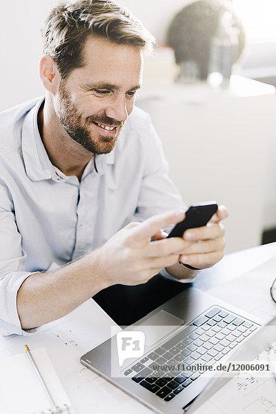 Porträt eines lächelnden Geschäftsmannes mit Smartphone am Schreibtisch in seinem Büro