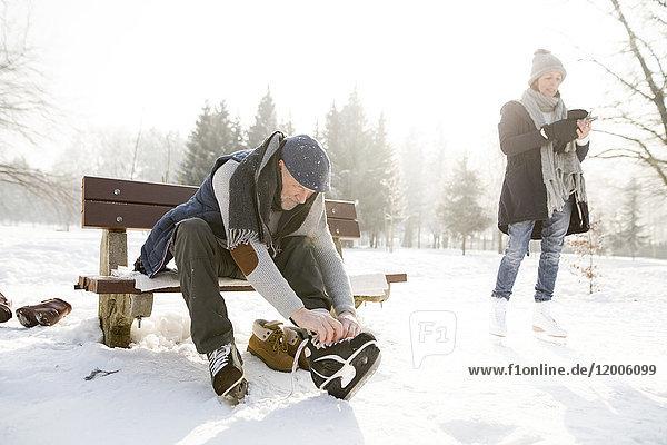 Älterer Mann sitzt auf einer Bank in der Winterlandschaft und setzt sich auf Schlittschuhe.