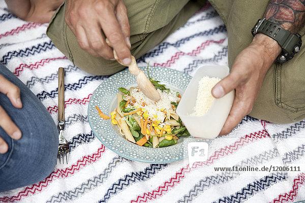 Mann dispergiert geriebenen Käse auf Nudelsalat während eines Picknicks