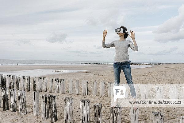Frau auf Holzpfählen am Strand stehend mit VR-Brille