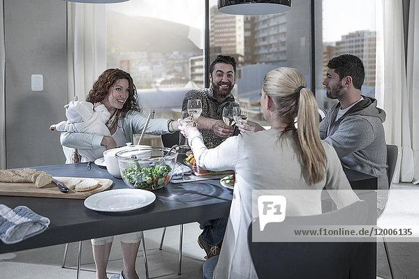 Familie und Freunde beim gemeinsamen Abendessen  die ihre Weingläser erheben.