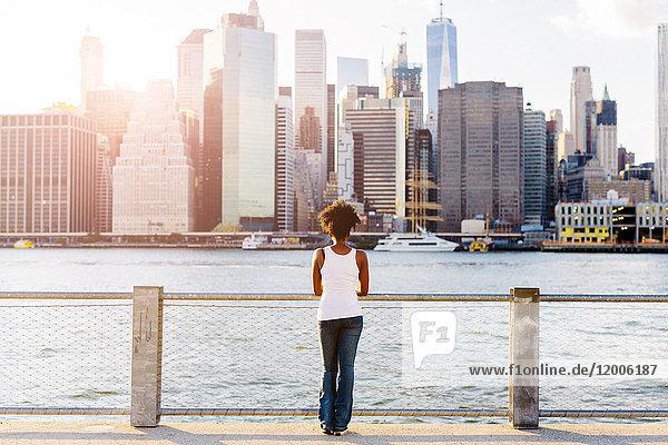 USA  New York City  Brooklyn  Frau am Wasser mit Blick auf die Skyline