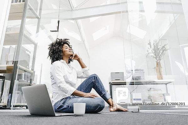 Junge Frau mit geschlossenen Augen sitzend auf dem Boden im Büro mit Laptop