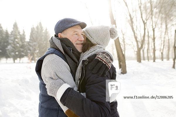Glückliches Seniorenpaar beim Umarmen in der Winterlandschaft