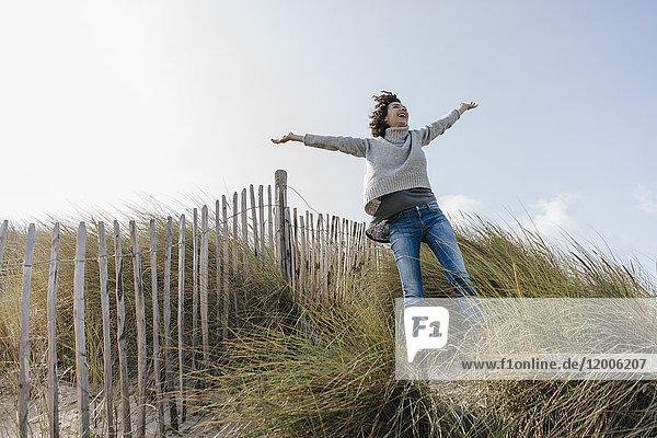 Glückliche Frau steht in der Stranddüne