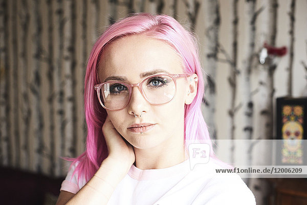 Portrait of young woman with pink hair  glasses and piercings