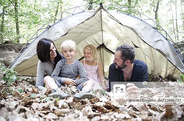 Glückliche Familie mit Zelt im Wald