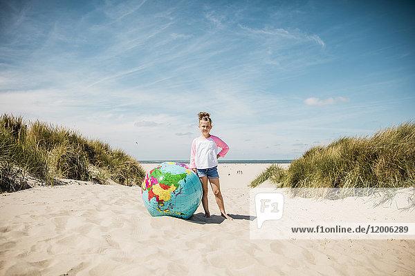 Mädchen mit Globus am Strand