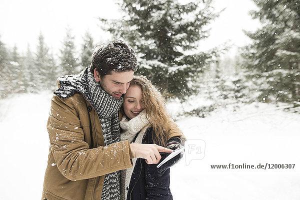Glückliches junges Paar steht mit dem Handy im verschneiten Winterwald